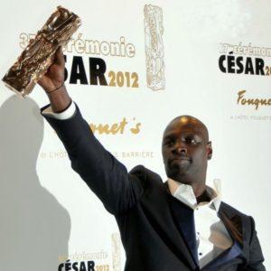 Homme noir brandissant un trophée de la main droite